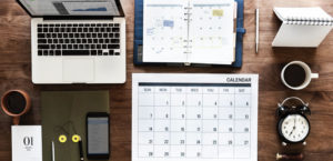 Mesa com notebook, calendário, agenda e outros objetos de escritório.