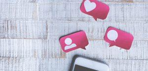 Smartphone em cima de uma mesa com recortes do ícone de coração em cima